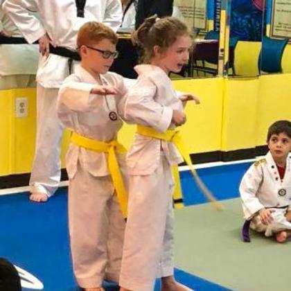 Kids helping each other in Taekwondo class