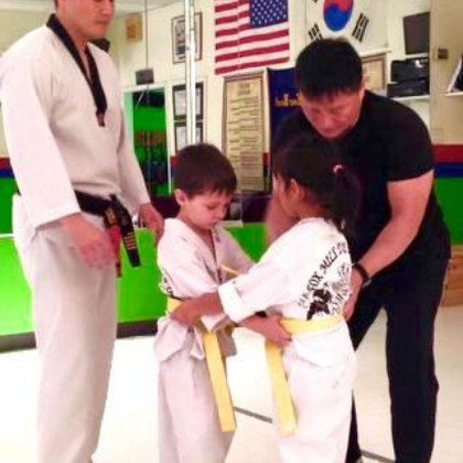Masters helping students with taekwondo techniques